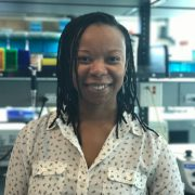 Headshot of Thelma Madzima. In the background are a series of pipette tip boxes and a mini vortexer.
